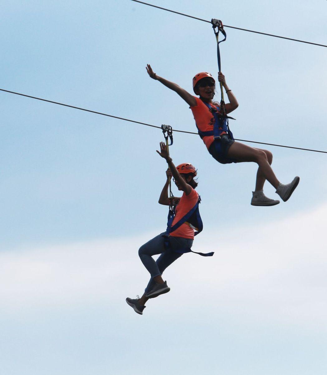 兩位民眾體驗戶外極限運動,從高雄愛河臨時搭建的平台,沿著150公尺的繩索體驗空中...