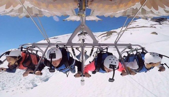 雪炫等乘坐滑翔傘從雪山飛行而下
