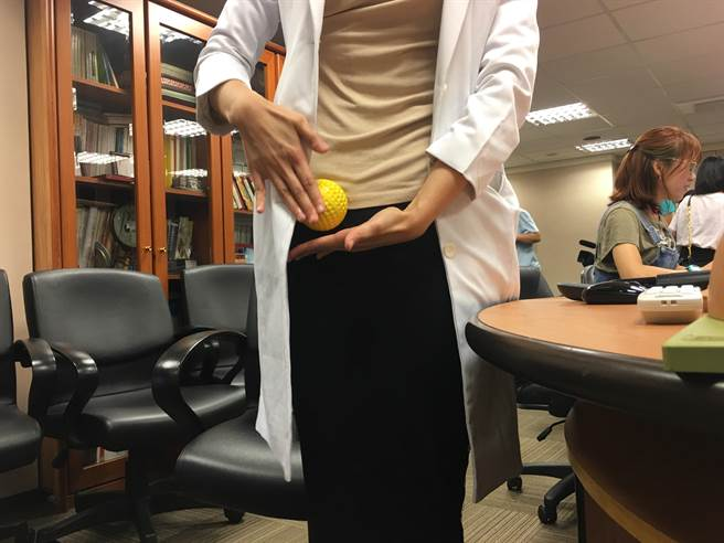民眾可使用按摩球,趴在瑜珈墊上按壓喀腰肌走過鼠蹊部的部位,放鬆骨盆底肌肉。(林周義攝)
